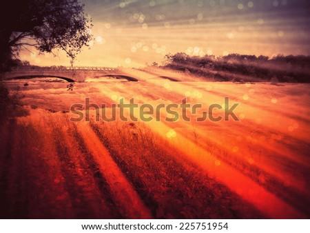 The sun shining on a field near a bridge. - stock photo