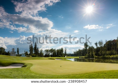 The sun shining over a golf course lined with buildings and trees