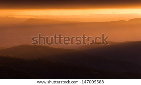 The sun shining through the mist on the Shenandoah Valley and Appalachian Mountains, seen from Skyline Drive in Shenandoah National Park at sunset.