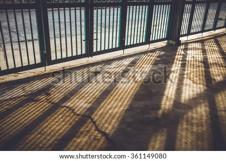 The sun was shining in the evening through the door fence, vintage filter - stock photo