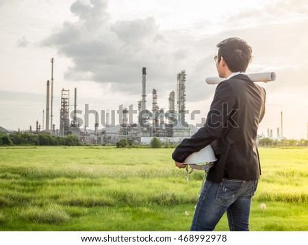 the sunlight to refinery engineer with engineer white safety helmet see drawing engineering in oil refinery building engineer structure in engineer heavy petrochemical refinery engineer industry.