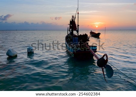 The sunset and a wooden boat on the sea - stock photo