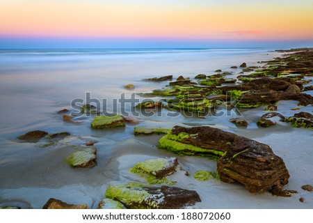 The sunset paints the opposite horizon over the Atlantic Ocean with color on a Florida beach with an outcropping of natural coquina stone. Waves are smooth and dreamy appearance from a long exposure. - stock photo