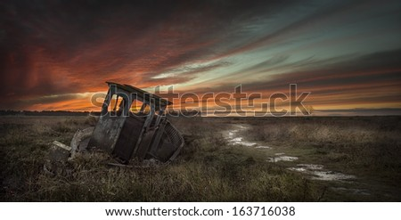 The sunsets on the old boat abandoned on Thornham Saltmarsh, Narfolk. For a moment the boat almost looks like it is still at sea. - stock photo