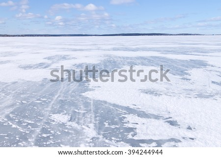 The surface of the lake covered with ice and blizzard - stock photo