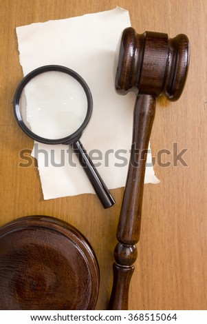 The surface of the table with the judge's hammer and a magnifying glass. - stock photo