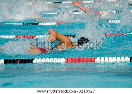 The swimmers compete hard in the high school league championships - stock photo