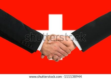 The Swiss flag and business handshake - stock photo