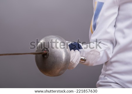 The sword in the hand of fencer wearing white fencing costume. Isolated on grey background - stock photo