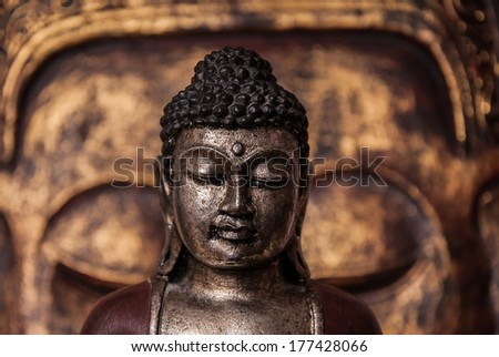 The symbol of the richness, of the founder of Buddhism, Buddha miniature statue sculpture with golden painted wood carved Buddha face on the background