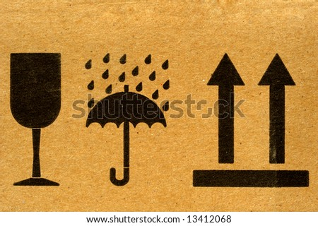 The symbols 'fragile', 'keep dry' and 'this way up' on cardboard.