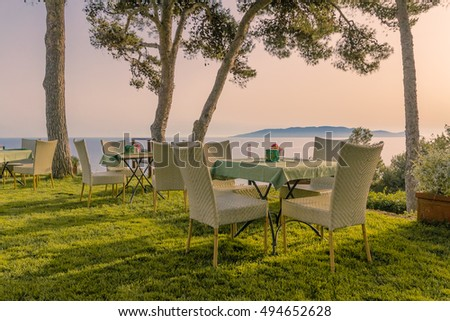 The table and cheers on the grass with view on the sea and iceland in the sunset light