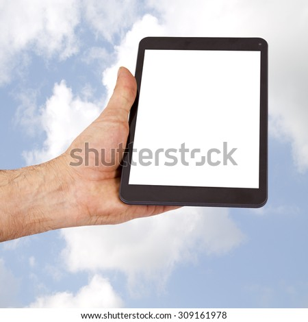 the tablet held in the hand with cloud background - stock photo