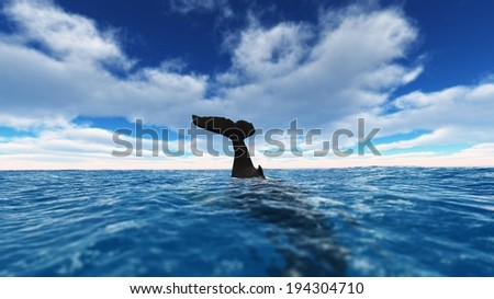The tail of a large whale as it dives into the ocean. - stock photo