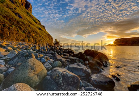 The Talisker Bay on the Isle of Skye in Scotland at sunset - stock photo