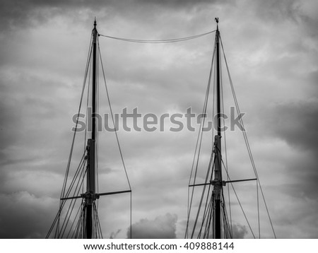The tall mast and riggings of a grand old sailing ship from yesteryear protrudes high into the dramatic cloudy skies. Sitting safe in port the sails were unfurled leaving the ship seemingly naked - stock photo