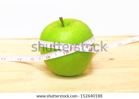The tape measure of body good health with a green apple - stock photo