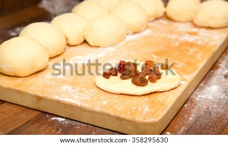 The tasty and ruddy bun will be made of the rolled dough circle with raisin. Not studio statement, photo of real process - stock photo