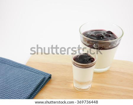 The tasty homemade blueberry panna cotta (Italian pudding dessert) in the small glass and blue cotton fabric on wooden board. - stock photo