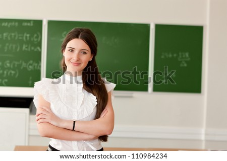 The teacher in the classroom on blackboard background.