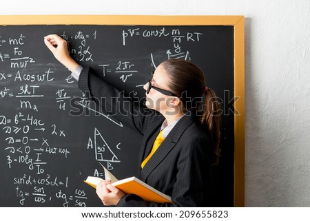The teacher writes on the blackboard