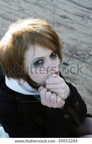 The tear-stained girl with the begun to flow ink looks in the camera. - stock photo