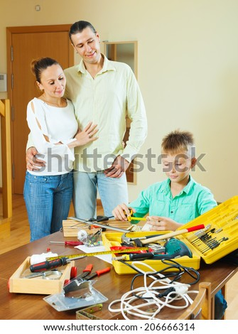 The teenager is doing something with their hands, the parents are watching - stock photo