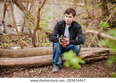 the teenager sits on the tumbled-down tree with a mug in hands, selective focus