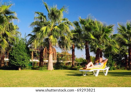 The teenager sunbathes near a palm tree - stock photo