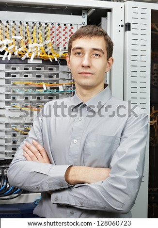 The telecom engineer stand in data center near telecommunication equipment.
