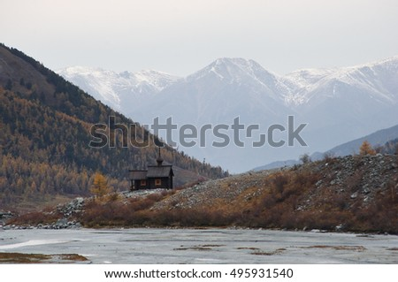 The temple church religious construction riding high in a mountain valley on a background of rocks and snow peaks under dramatic gloom dark sky Belukha, Altai mountains, Siberia, Russia