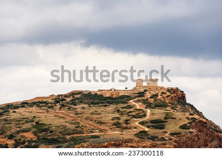 The Temple of Poseidon at Sounio, Greece against a cloudy sky, shot taken from accross the bay - stock photo