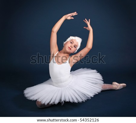 The ten years' girl dances in a ballet tutu on a dark blue background
