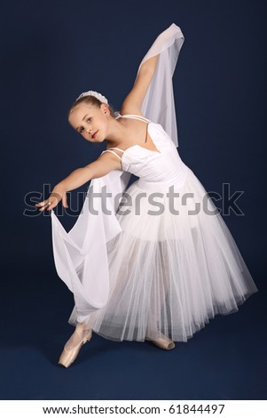The ten years' girl dances in a ballet tutu on a dark blue background - stock photo