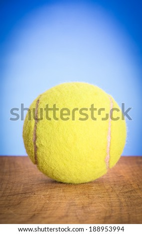 The tennis ball on blue background with vignette - stock photo