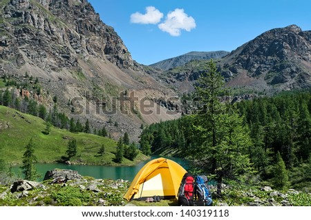 the tent, two backpacks and two pairs boots near a mountain lake in the summer  - stock photo