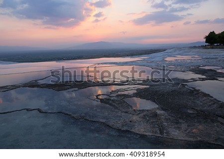 """The terraces of Pamukkale, which means """"cotton castle"""" in Turkish, is natural site in southwest Turkey.  Shot at sunset with the sky reflecting in the terrace pools.  - stock photo"""