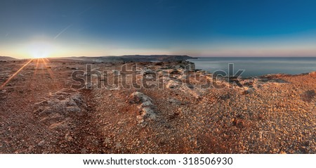 The terrain at Majjistral Park during sunrise.  One look at the stones and colour and you could easily think you're on Mars. - stock photo