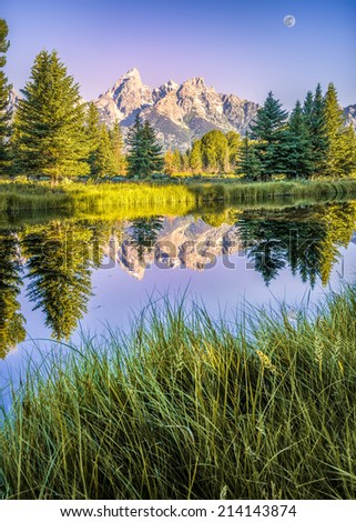 The Teton range's reflection upon the Snake River after dawn at Schwabacher Landing in Grand Teton National Park, WY - stock photo
