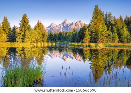 The Teton range's reflection upon the Snake River.  Photographed at dawn at Schwabacher Landing in Grand Teton National Park, WY - stock photo