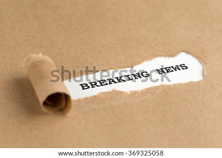 The text BREAKING NEWS appearing behind torn brown paper - stock photo