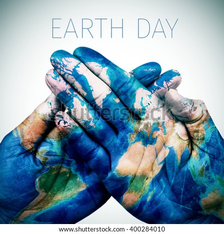 the text earth day and the hands of a young man put together patterned with a world map (furnished by NASA) - stock photo