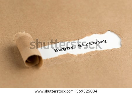 The text Happy Birthday appearing behind torn brown paper - stock photo