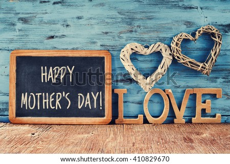 the text happy mothers day written in a chalkboard placed next to some wooden letters forming the word love and some rustic handmade hearts, against a rustic blue background - stock photo