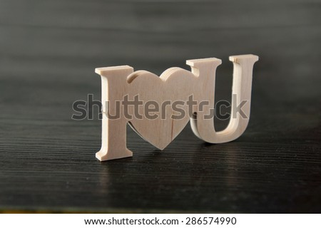 The text I love you carved out of wood paper - stock photo