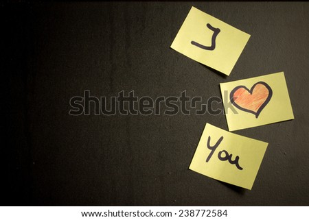 the text I Love You on little  peaces of paper over a blackboard background - stock photo