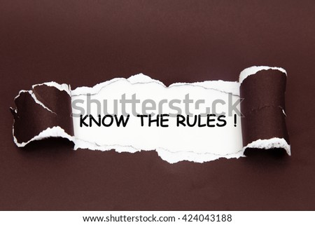 The text KNOW THE RULES! behind torn black paper - stock photo