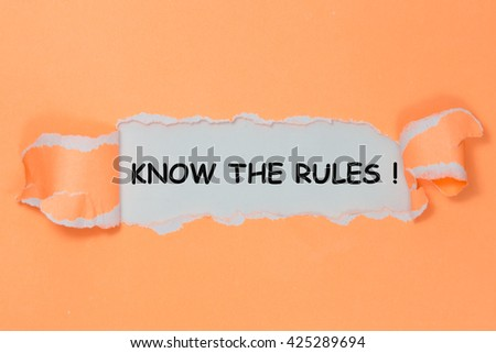 The text KNOW THE RULES! behind torn paper - stock photo