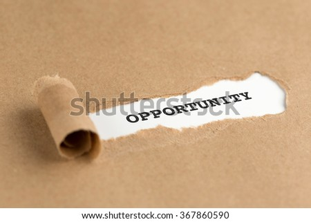 The text OPPORTUNITY appearing behind torn brown paper - stock photo