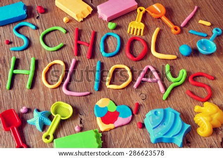 the text school holidays made from modelling clay of different colors and some beach toys such as toy shovels and sand moulds, on a rustic wooden surface - stock photo